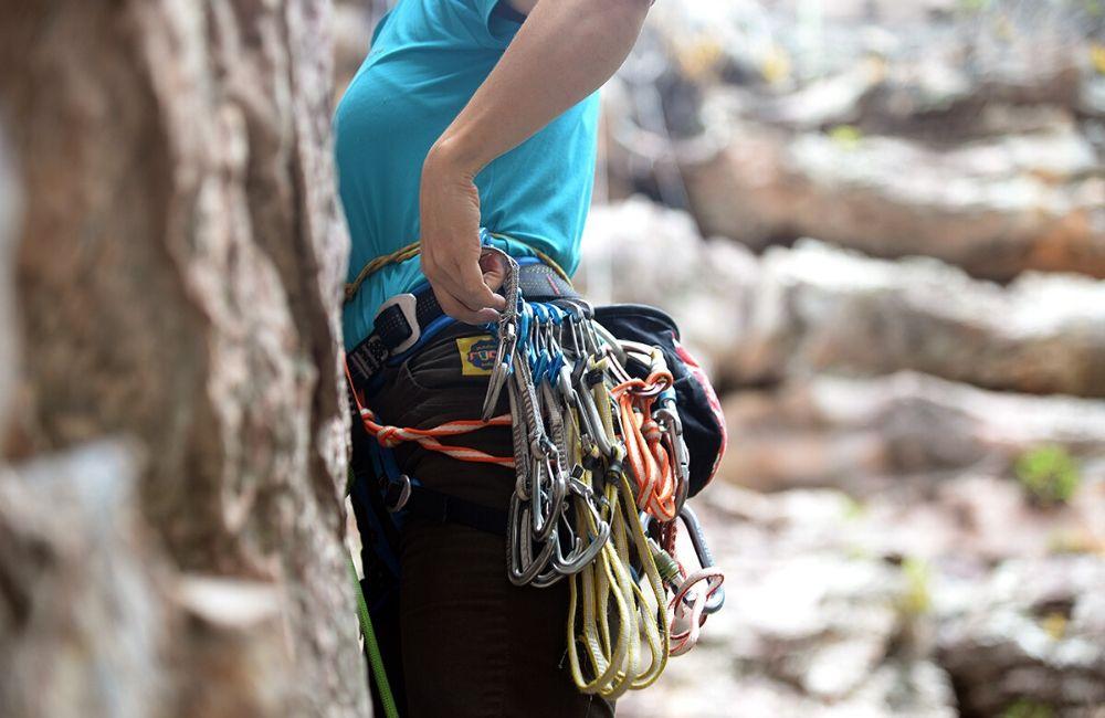 Foto de escaladora usando cadeirinha de escalada, ela está de perfil retirando uma costura do rack